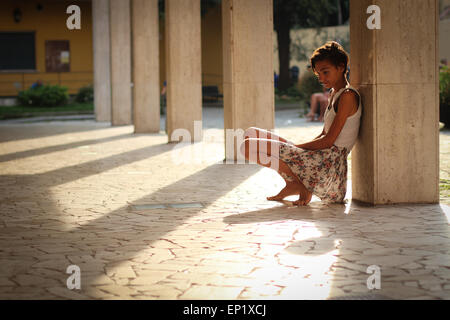 Girl leaning against a pillar in a courtyard - Stock Photo