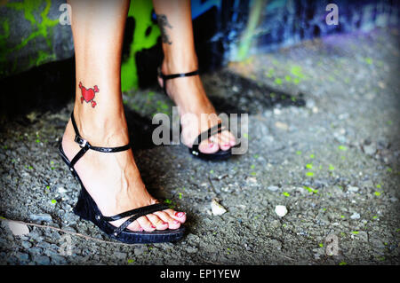 A woman wearing high heel shoes with a heart tattooed on her ankle - Stock Photo