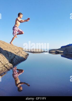 Boy jumping off a rock into the sea - Stock Photo