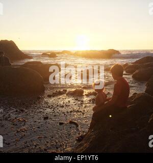 Two boys sitting on rocks at the beach at sunset, Dana Point, California, USA - Stock Photo