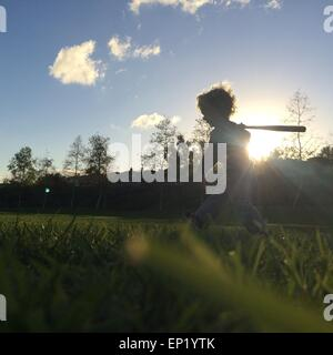 Boy playing with baseball bat - Stock Photo