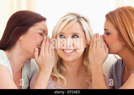 Young woman being told two secrets at a time - Stock Photo