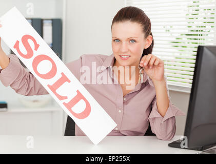 Businesswoman shows sold sign - Stock Photo