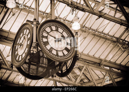 A large four-faced clock hangs in the middle of the main concourse. 'Meeting 'under the clock' is a traditional - Stock Photo