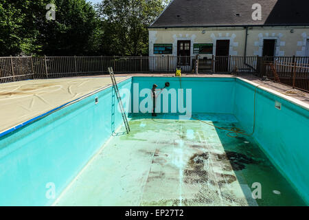 Karcher pressure washer power jet wash patio attachment being used by middle aged man wearing shorts to clean swimming - Stock Photo