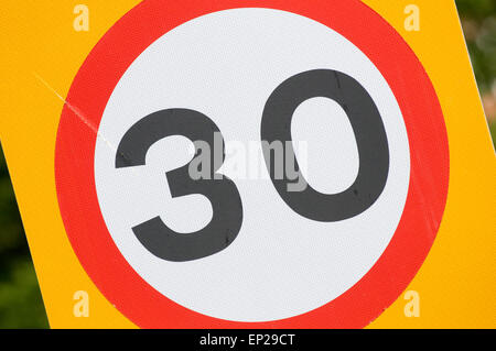 30 mph miles per hour thirty speed limit limits speeding restrictions restricted urban road roads road sign signs - Stock Photo