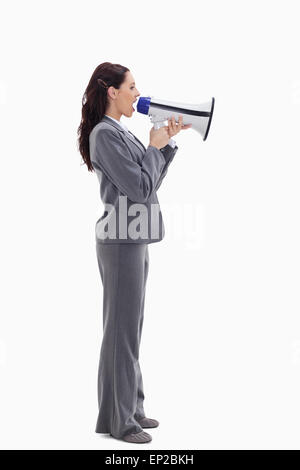 Profile of a businesswoman speaking loudly in a megaphone - Stock Photo
