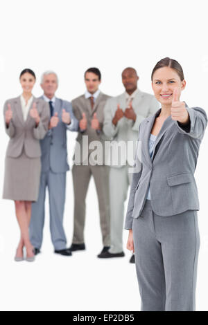 Saleswoman with thumb up and her team behind her - Stock Photo