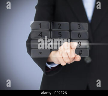 Business woman entering pin on digital number pad - Stock Photo