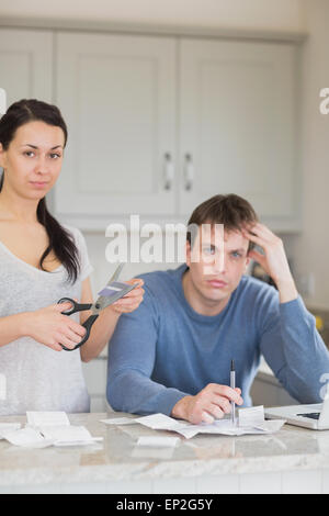 Woman cutting up credit card with man calculating finances - Stock Photo