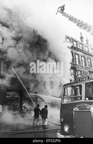 Fire at Maryhill Road Glasgow. Fire breaks out in an unoccupied furniture shop spreading along the row of shops - Stock Photo