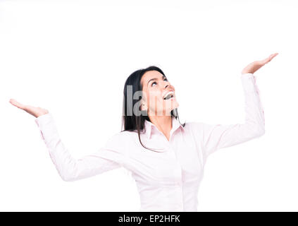 Laughing businesswoman presenting something on palm over white background. Looking up - Stock Photo