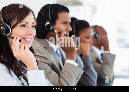 Smiling call centre employee working while accompanied by her team - Stock Photo