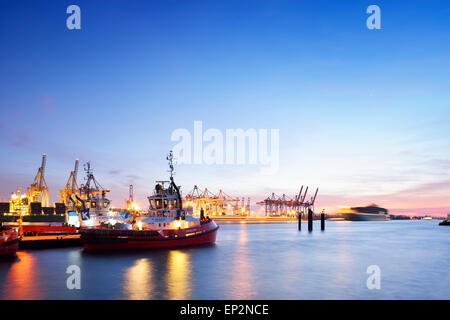 Germany, Hamburg, container harbor Waltershof with tugboats at blue hour - Stock Photo