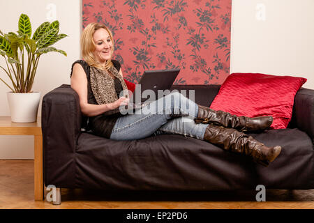Young woman on a sofa using a laptop - Stock Photo