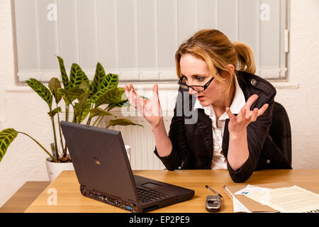 Young woman angry with her laptop - Stock Photo