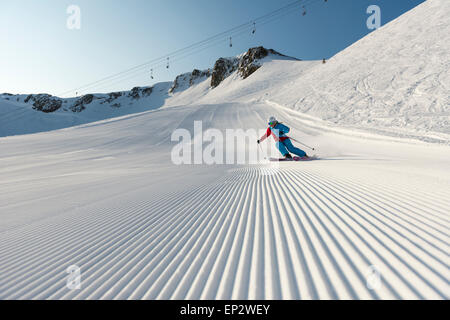Squaw Valley skier with beautiful groomed snow beneath the palisades on Siberia Lift at Squaw Valley Ski Resort, CA