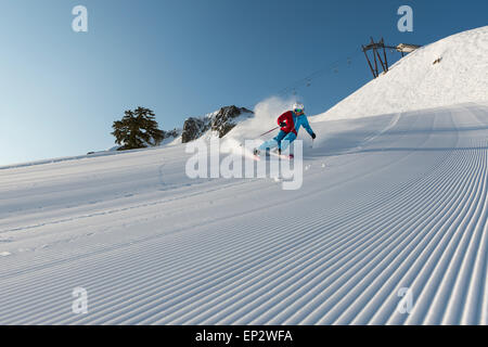 Squaw Valley skier with beautiful groomed snow beneath the palisades on Siberia Lift at Squaw Valley Ski Resort, - Stock Photo