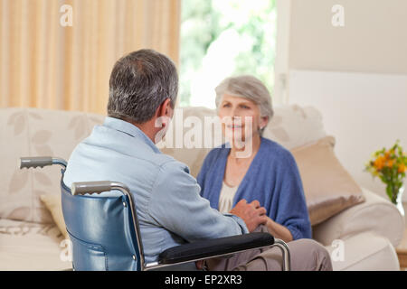 Senior couple talking in the living room at home - Stock Photo