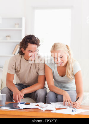 Happy couple calculating their expenses - Stock Photo
