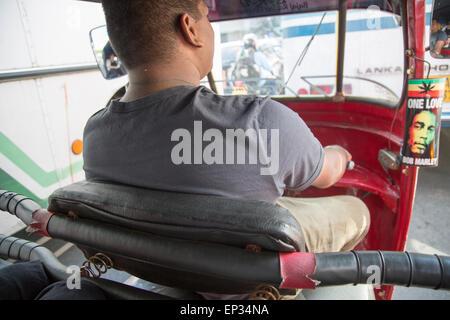 Motorised rickshaw Tuk Tuk driver in traffic of central city area of Colombo, Sri Lanka, Asia
