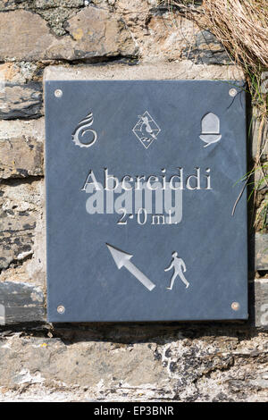 Sign on stone wall at Porthgain showing distance and direction to Abereiddi, Pembrokeshire Coast National Park, - Stock Photo