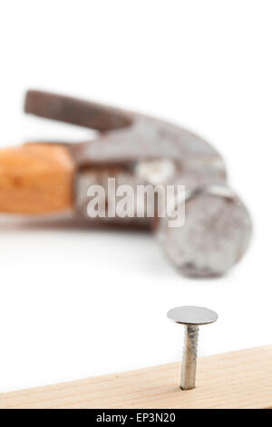 Half nail sticking in a plank and a hammer lying behind - Stock Photo