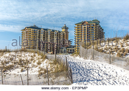 A pathway up the fence lined sand dune with a beautiful condominium on the horizon backed by gorgeous blue sky with - Stock Photo