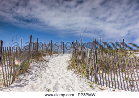 A pathway up the white sand dune lined by fence, disappearing into the beautiful blue sky with thin white clouds - Stock Photo