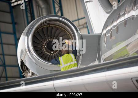 Aircraft mechanic inspecting airplane's jet engine - Stock Photo