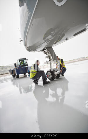 Ground crew attaching a tow bar to an aircraft's nose landing gear with a towing tractor ready to pushback the airplane - Stock Photo