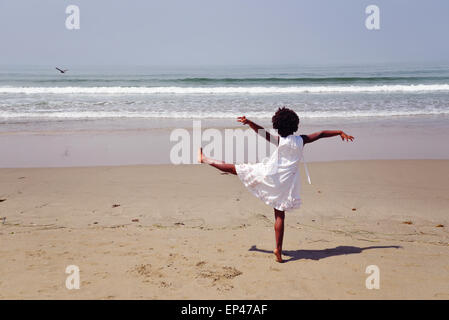 Rear view of an african american girl standing on one leg on the beach - Stock Photo