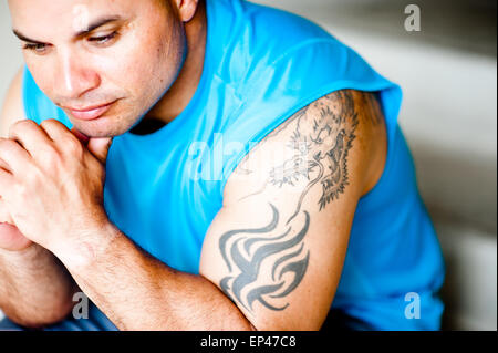 Portrait of a young man with tattoos sitting on a step - Stock Photo