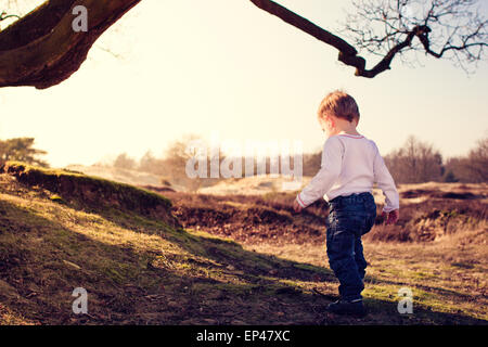 Toddler exploring the countryside - Stock Photo