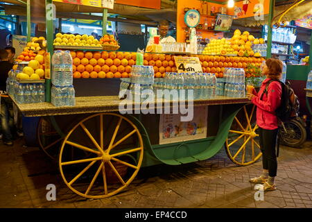 Orange Juice seller at the nightly bazaar and food stalls at the Jamaa el Fna, Marrakesh Medina. Morocco - Stock Photo
