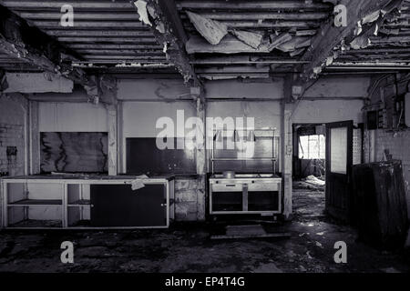 Black and white derelict abandoned kitchen, with severely ruined ceiling - Stock Photo