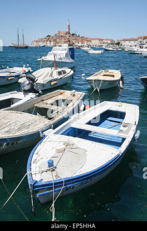 Boats anchored in the marina with a view of other boats sailing in the sea and the town in the background in Rovinj, - Stock Photo