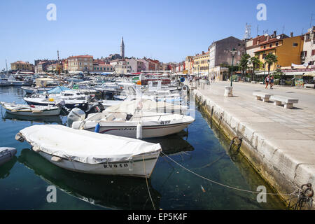 A large group of boats anchored in the marina with a view of the Saint Euphemia church and people walking on the - Stock Photo