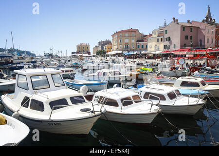 A large group of boats anchored in the marina with a view of people walking on the city promenade in Rovinj, Croatia. - Stock Photo