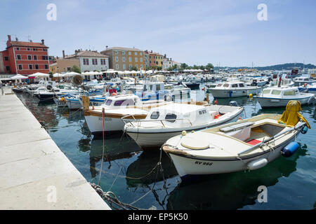 A large group of boats anchored in the marina with a view of the city promenade in Rovinj, Croatia. - Stock Photo