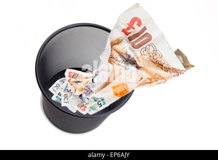 Image of £10 note screwed up being thrown away in a wastepaper bin on white to illustrate wasting pounds GBP Sterling - Stock Photo