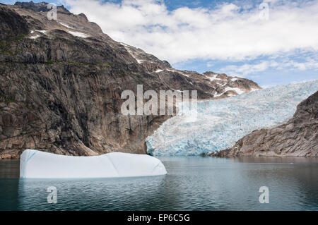 Floating iceberg in front of glacier in Prince Christian Sound, southern Greenland - Stock Photo