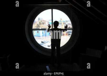 10 year old English boy looking out of the lighthouse window in Trinity Buoy wharf lighthouse. - Stock Photo