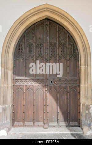 Medieval decorative, wooden studded, arched double door with ancient stone surround - Stock Photo