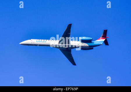 Luxair Embraer ERJ-145LU flying in the blue sky of Luxembourg - Stock Photo