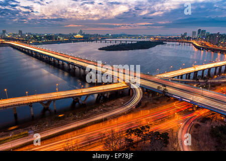 Traffic blurs across a bridge on the Han River as dusk settles in over Seoul, South Korea. - Stock Photo