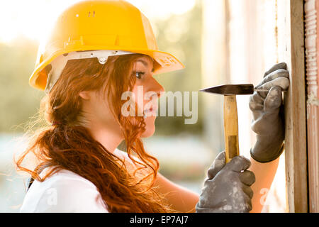 Woman Bricklayer with Helmet Hitting a Nail with a Hammer - Stock Photo