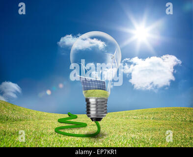 Light bulb showing solar panels and turbines in a field - Stock Photo
