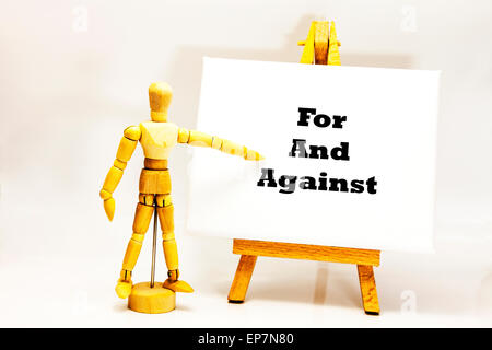 Wooden man with white board pointing at words 'For And Against' pros and cons choice choose choices Yes No Maybe - Stock Photo