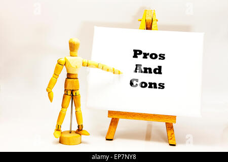 Wooden man with white board pointing at words 'Pros And Cons' for against list behalf of contrā contra The positive - Stock Photo